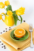 Yellow jug with yellow tulips and juicy oranges for breakfast — Stock Photo