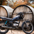 Black motorcycle on a background with a large barrel for wine — Stock Photo