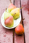 Tasty fragrant pear lying on a white plate — Stock Photo