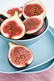 Ripe figs lying on a blue plate on a pink napkin — Stock Photo