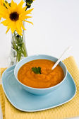 Pumpkin soup in a blue plate and a bouquet of yellow flowers — Stock Photo