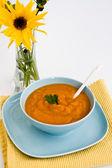 Dýňová polévka v modré desky a kyticí žlutých — Stock fotografie