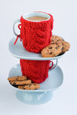 Two blue cups in knitted covers and chocolate cookies — Stock Photo