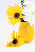 Yellow jug with yellow and white flowers on a light background — Stock Photo