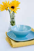 Blue plate and bouquet of yellow flowers — Foto de Stock