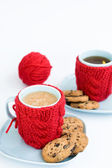 Two blue cups in knitted covers and chocolate cookies and a ball of knitting — Stock Photo