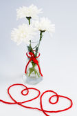 White flowers in a small glass vase with a red bow and two hearts from threads — Stock Photo
