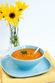 青い板と黄色の花の花束でカボチャのスープ — ストック写真