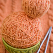 Stock Photo: Two peach-colored ball of yarn are in plate and needles