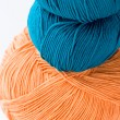 Stock Photo: Two skeins of yarn and turquoise orange yarn