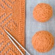Stock Photo: Orange balls, knitted pattern and knitting needles
