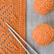 Orange balls, knitted pattern and knitting needles — Stock Photo #38665271