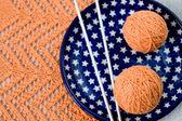 Pomarańczowe kulki, z dzianiny wzór i dziewiarskie nedles — Zdjęcie stockowe