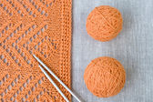 Orange balls, knitted pattern and knitting needles — Stock Photo