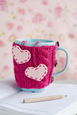 Blue cup in pink sweater with felt hearts standing on an open notebook — Foto de Stock