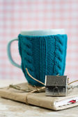 Blue cup in a blue sweater standing on an old notebook — Foto de Stock
