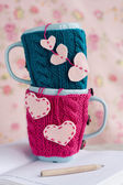 Two blue cups in blue and pink sweater with felt hearts on an notebook — Stock Photo