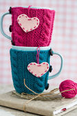 Two blue cups in blue and pink sweater with felt hearts on an notebook — Foto de Stock