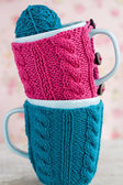 Two blue cups in blue and pink sweater with ball of yarn for knitting — Stock Photo
