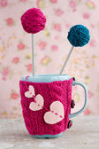 Blue cup in pink sweater with felt hearts with ball of yarn — Stock Photo