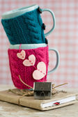 Two blue cups in pink and blue sweater on an old notebook — Foto de Stock
