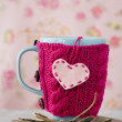 Blue cup in pink sweater standing on old notebook — Stock Photo #39568077