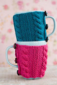 Two blue cups in blue and pink sweater — Стоковое фото