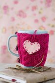 Blue cup in a pink sweater standing on an old notebook — Stock Photo