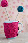 Blue cup in pink sweater with ball of yarn — Стоковое фото