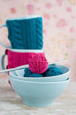 Two blue cups in blue and pink sweater with balls — Foto de Stock