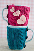 Two blue cups in blue and pink sweater with felt hearts — Стоковое фото
