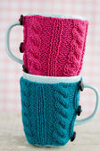 Two blue cups in blue and pink sweater — Stock Photo
