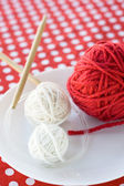 Bright balls of yarn and knitting needles on a polka dot background — Stock Photo