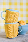 Two blue cups in yellow sweater on a fabric — Stock Photo