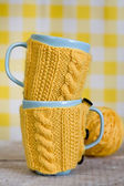 Two blue cups in yellow sweater on a fabric background — Stock Photo