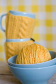 Two blue cups in yellow sweater on a fabric background — Stok fotoğraf
