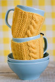 Two blue cups in yellow sweater on a fabric background — Foto Stock