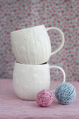 Two white cups of bright balls of yarn for knitting — Stock Photo