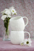 Two white cups and a bouquet of white flowers — Foto Stock