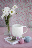 One white cup on a background, vintage notebook and flower — Foto Stock