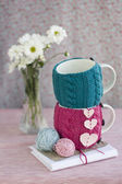 Two cups in blue and pink sweater with felt hearts — Stock Photo