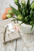 Bouquet of delicate pink tulips on a wooden background, vintage note pad and bright balls of yarn — Stockfoto