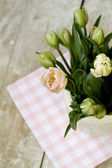 Bouquet of delicate pink tulips on the tablecloth — Stock Photo