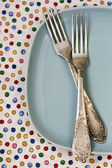Two forks lying on blue plate on bright background — Stock Photo