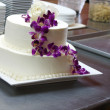 White Wedding Cake with purple orchids - Foto Stock