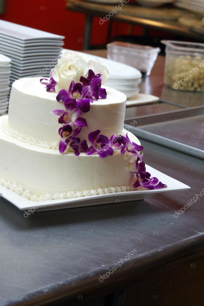 Gâteau de mariage blanc avec orchidées pourpres — Photographie ...