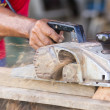 Carpenter working with electric planer — Stock Photo #14445909