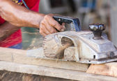 Carpinteiro trabalhando com plaina elétrica — Foto Stock