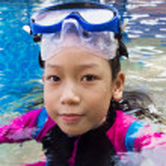 Girl swimming wearing goggles — Stock Photo