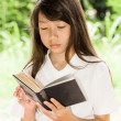 Asian girl reading book — Stock Photo